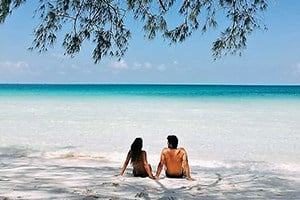 couple in swimming suits seat on beach pristine waters