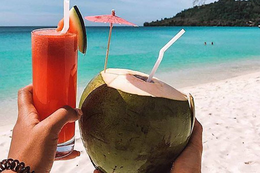 Cocktail and coconut. Blue sea background
